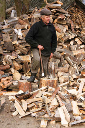 Man stands next to the deck leaning on an axe