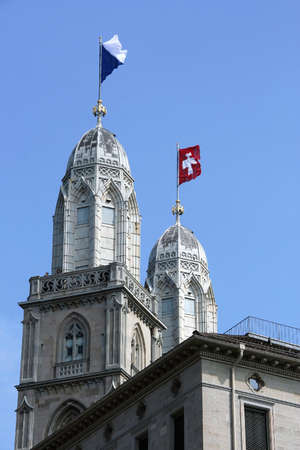 grossmunster cathedral: National flag and canton flag on towers of Grossmunster Cathedral - major landmarks of Zurich cityscape Switzerland Stock Photo