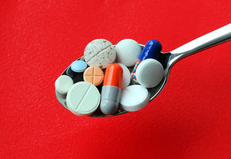 Silver spoon full of tablets Stock Photo - 14788459