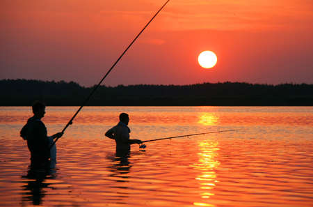 Father and son fishing in lake at sunset