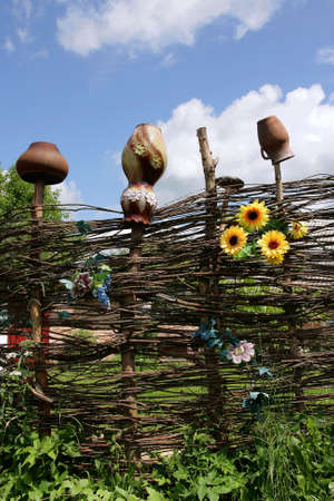Rural fence with jugs and sunflowers against the sky photo