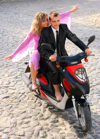 Beautiful young love couple enjoying themselves while ridding on scooter  photo
