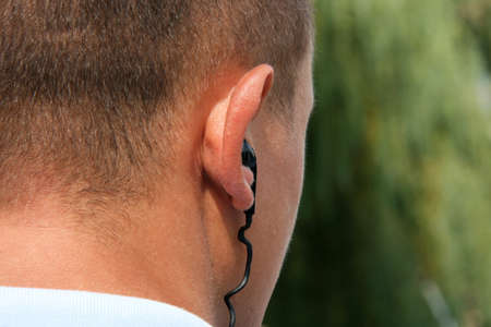 listening back: Back of male head with earphone