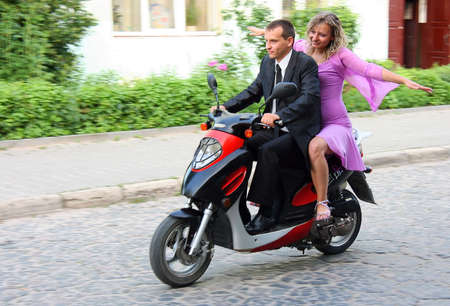woman motorcycle: Beautiful young love couple enjoying themselves while ridding on scooter