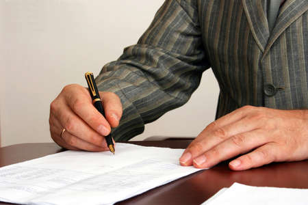parer: The man in a striped jacket signs the document. In a picture the hand with pen and a sheet of paper on a table is visible
