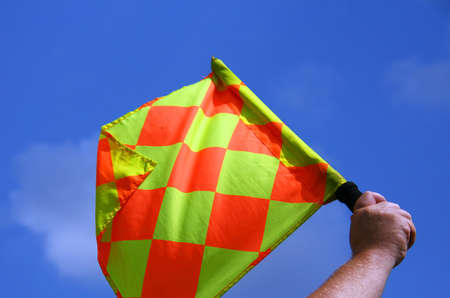 Male hand holding a checkered flag on a background of the blue sky with clouds photo