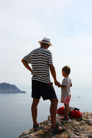 Man and boy enjoying the sea view from the top of the mountain  photo