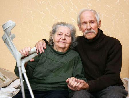 Grandpa in a dark sweater gently embracing grandmother who keeps him at arm crutches photo