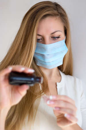 Woman in mask hand holding medicine health care syrup. Stock Photo - 17601136