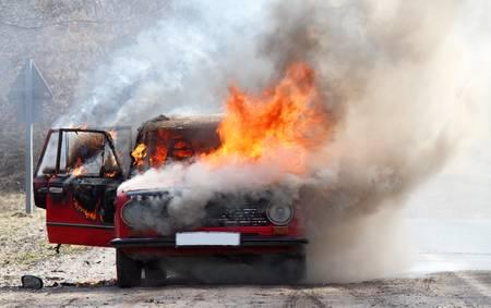 Burning car on desert rural road 写真素材