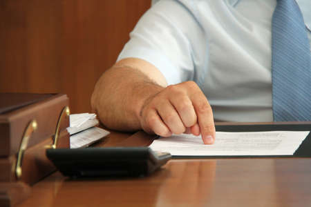 Hand of businessman at desk with document point finger on paper. Shallow depth of field. Stock Photo