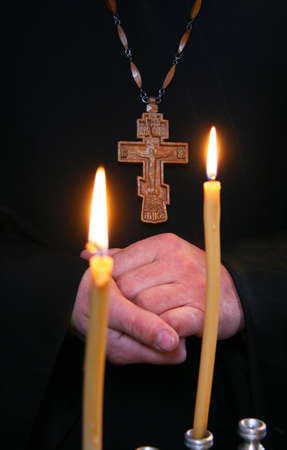 Hands Orthodox priest and a cross on a background of candles  Shallow depth of field  Stock Photo