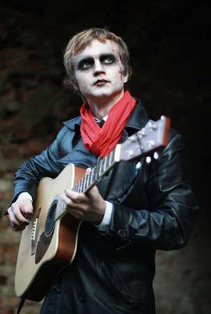 stage makeup: LUTSK - 1 novembre: Chitarrista sul palco make-up in cappotto di pelle nera con una sciarpa rossa a Halloween il 1 novembre 2013 a Lutsk, Ucraina. Profondit� di campo. Focus sugli occhi.