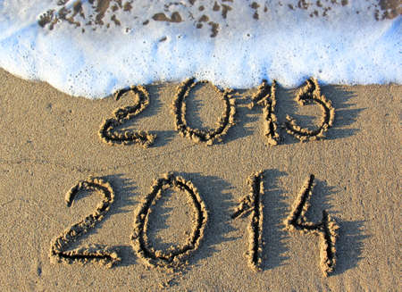 Happy New Year 2014 replace 2013 concept on the sea beach  Stock Photo