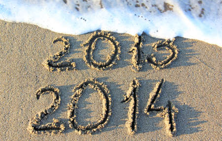 Happy New Year 2014 replace 2013 concept on the sea beach Stock Photo - 24384685