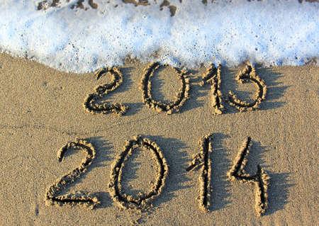 zastąpić: Happy New Year 2014 replace 2013 concept on the sea beach  Zdjęcie Seryjne