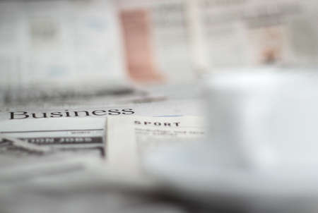 Newspapers and coffee cup macro shot with shallow depth of field photo