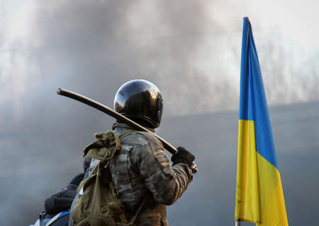 A man in a helmet with a stick at the Ukrainian flag