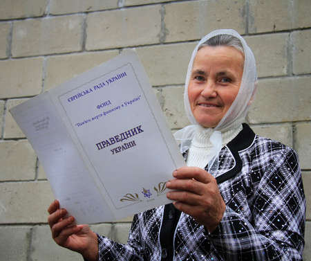 a righteous person: RATNO, UKRAINE - NOVEMBER 08- A woman holds the certificate Righteous Ukraine on November 08 2013.  Editorial