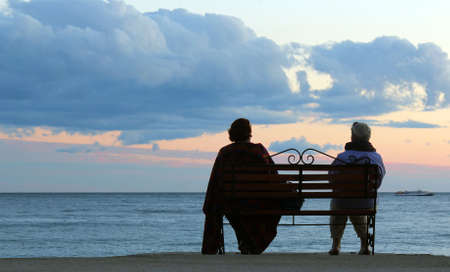 Elder couple couple sitting on a seaside bench enjoying the sunset over the sea  Stock Photo