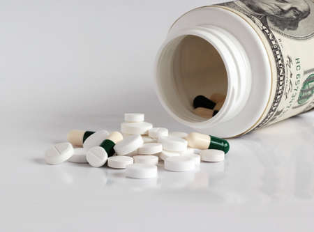 Money with pills, high costs of expensive medication concept  Stock Photo