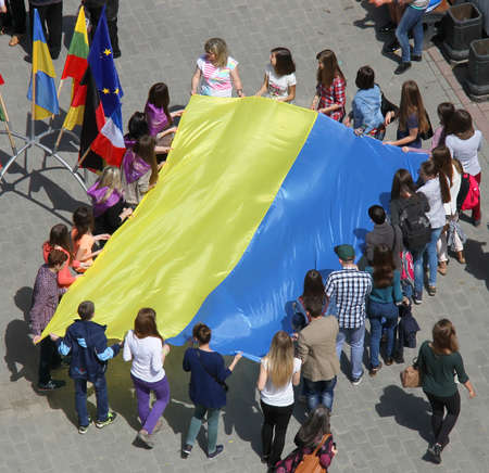 mobs: Lutsk, Ukraine - May 17, 2014: young people holding a big flag of Ukraine during Europe Day