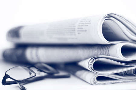 A stack of newspapers with glasses  Shallow depth of field  Stock Photo