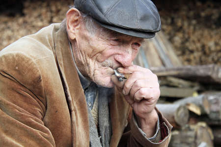 stary: STARY, UKRAINE - OCTOBER 17 - Ukrainian peasant smoking a roll your own cigarette in Stary on October 17, 2013. Poverty is a big problem in Ukraine.