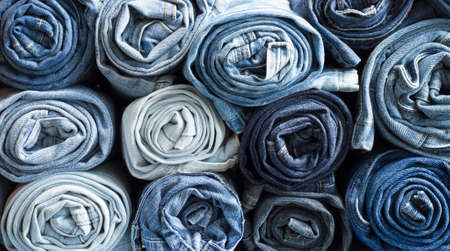 Roll blue denim jeans arranged in stack