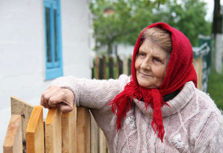 privatization: CHEREVAHA, UKRAINE - MAY 16 - An unidentified senior woman standing near house in Cherevaha on May 16, 2014. Land privatization is a big problem in Ukraine.