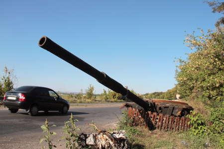 collisions: SLAVYANSK, UKRAINE - SEPTEMBER 05,2014: Destroyed tank on the road near Slavyansk after armed conflict on September 05 2014 in Slavyansk, Ukraine.  Editorial
