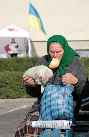 elector: LUTSK, UKRAINE - 15 OCTOBER 2014: An unidentified elderly woman with a piece of bread in your mouth sitting at outdoor pending meeting on October 15, 2014 in Lutsk, Ukraine