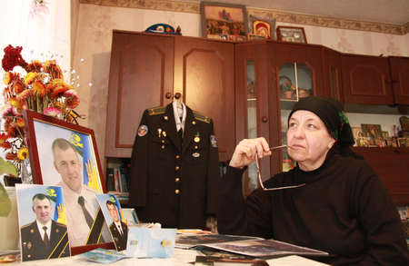 deceased: ZALIZNYCIA, UKRAINE - NOVEMBER 14: The mother of the deceased in the area ATO Ukrainian officer sitting in the room before photographs son in Zaliznycia, Ukraine on November 14, 2014