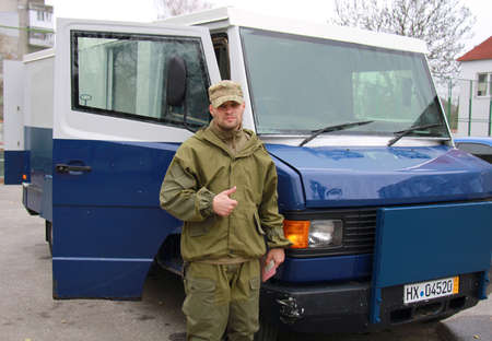 armored car: LUTSK, UKRAINE - NOVEMBER 13: Ukrainian army officer stands near an armored car that is sent to the ATO area in Lutsk, Ukraine on November 13, 2014 Editorial