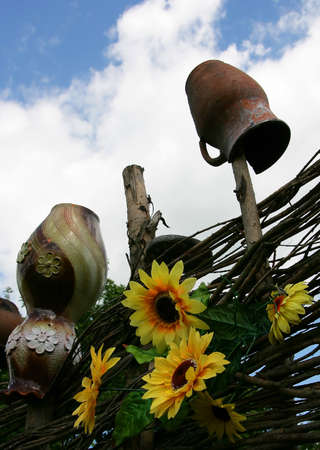 interweaving: Rural fence with jugs and sunflowers against the sky Stock Photo