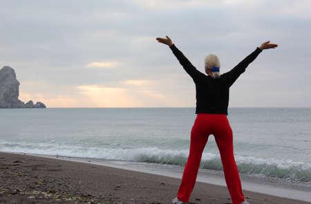 manos levantadas al cielo: Mujer joven con las manos levantadas de pie sobre la arena y mirando a un cielo Foto de archivo