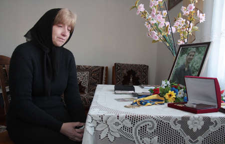 saddened: MENCHYCHI, UKRAINE - FEBRUARY 02: The mother of the deceased in the area ATO Ukrainian soldier sitting in the room before photographs son in Menchychi, Ukraine on February 02, 2015