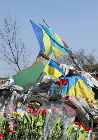 barricades: KIEV, UKRAINE - MARCH 3, 2014: Ukrainian revolution, Euromaidan. Days of national mourning for killed defenders. Flowers on barricades defenders. Editorial