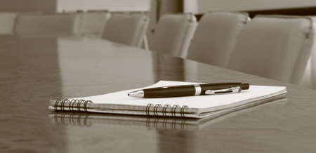 Closeup of notepad on table in empty conference room before business meeting Stock Photo