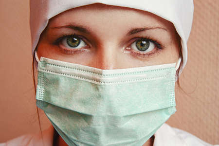surgeon mask: Portrait of young caucasian woman model behind surgeon mask