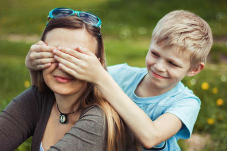 blind child: Son mother closes her eyes in the park in spring