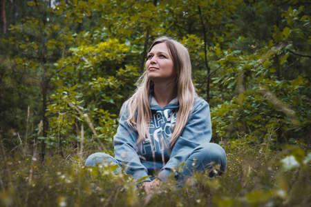 Frau mittleren Alters meditierend in einem Wald auf einem Gras sitzt