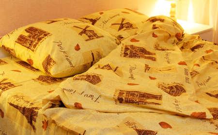 cama: Primer plano de las hojas de ropa de cama y almohadas en la cama y la lámpara