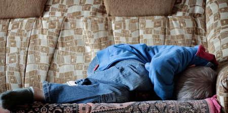 maltrato infantil: Muchacho asustado en jeans acurrucada en la cama Foto de archivo