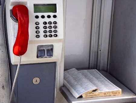 directorio telefonico: Teléfono público y un directorio de teléfono antiguo en caja de llamada
