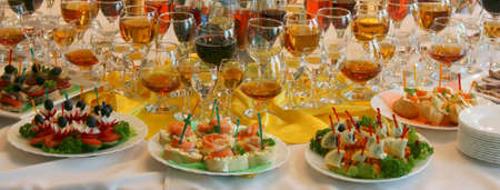 Plates with sandwiches and glasses of wine on a table at restaurant Stock Photo
