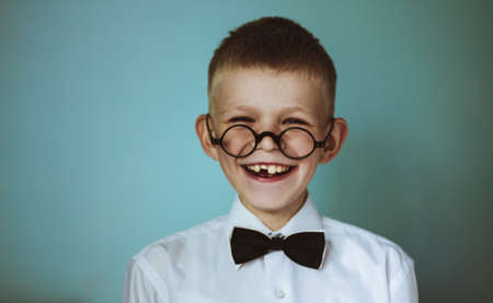 toothless: A young toothless boy wearing glasses and a black bow tie Stock Photo