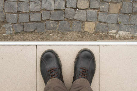 Looking down man feet on cobbled road Stock Photo