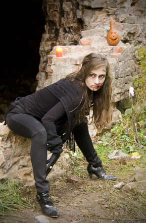 bloodthirsty: Bloodthirsty zombie with halloween pumpkin in ruins of the castle