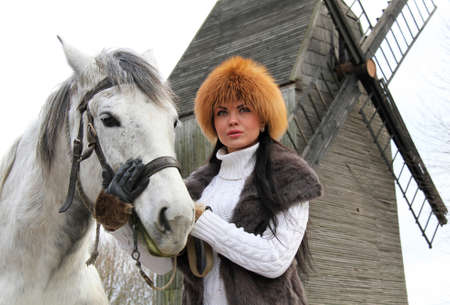 longing: The girl in a fur hat and a horse on the background of an old windmill Stock Photo